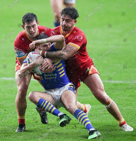 Leeds Rhinos' Jack Walker is tackled by Catalans Dragons' Matt Whitley and Arthur Romano