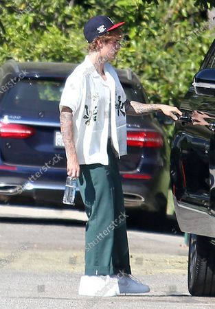 Justin Bieber wears green pants and a baseball cap in Beverly Hills