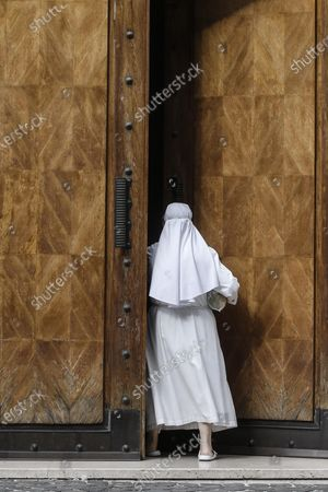 A nun enters a building where the house of Cardinal George Pell is located in Rome, Italy, 30 September 2020.