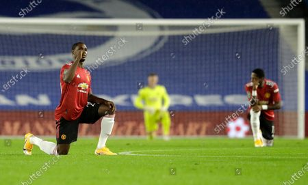 Manchester United's Odion Ighalo gestures as he kneels ahead of the English League Cup fourth round soccer match between Brighton and Manchester United at Falmer Stadium in Brighton, England