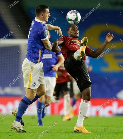 Manchester United's Odion Ighalo, right, kicks the ball away from Brighton's Lewis Dunk during the English League Cup fourth round soccer match between Brighton and Manchester United at Falmer Stadium in Brighton, England