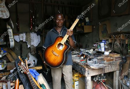 Adicko Pierre, 62, an Ivorian luthier holds a guitar made by him in his workshop in Abobo, a district of Abidjan, Ivory Coast, 30 September 2020, a day before International Music Day. International Music Day is celebrated every year on October 1. It was established in 1975 by the International Music Council (CIM), itself founded in 1949 by UNESCO. Music plays an essential role for many people and is a powerful vector for intercultural rapprochement. The International Day dedicated to it aims primarily to highlight its importance and that of musicians on a global scale, and to promote the social value that its status as a common language confers on it as a factor of peace and understanding.
