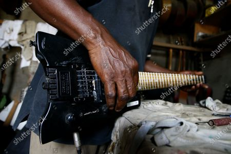 Adicko Pierre, 62, an Ivorian luthier plays a guitar made by him, in his workshop  in Abobo, a district of Abidjan, Ivory Coast, 30 September 2020, a day before International Music Day. International Music Day is celebrated every year on October 1. It was established in 1975 by the International Music Council (CIM), itself founded in 1949 by UNESCO. Music plays an essential role for many people and is a powerful vector for intercultural rapprochement. The International Day dedicated to it aims primarily to highlight its importance and that of musicians on a global scale, and to promote the social value that its status as a common language confers on it as a factor of peace and understanding.