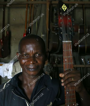 Adicko Pierre, 62, an Ivorian luthier holds a guitar made by him in his workshop in Abobo, a district of Abidjan, Ivory Coast on September 30, 2020, a day before International Music Day. International Music Day is celebrated every year on October 1. It was established in 1975 by the International Music Council (CIM), itself founded in 1949 by UNESCO. Music plays an essential role for many people and is a powerful vector for intercultural rapprochement. The International Day dedicated to it aims primarily to highlight its importance and that of musicians on a global scale, and to promote the social value that its status as a common language confers on it as a factor of peace and understanding.
