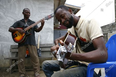 Adicko Pierre, 62, an Ivorian luthier (L) plays a guitar made by him, in the yard of his workshop  in Abobo, a district of Abidjan, Ivory Coast on September 30, 2020, a day before International Music Day. International Music Day is celebrated every year on October 1. It was established in 1975 by the International Music Council (CIM), itself founded in 1949 by UNESCO. Music plays an essential role for many people and is a powerful vector for intercultural rapprochement. The International Day dedicated to it aims primarily to highlight its importance and that of musicians on a global scale, and to promote the social value that its status as a common language confers on it as a factor of peace and understanding.