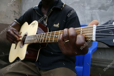 Adicko Pierre, 62, an Ivorian luthier plays a guitar made by him, in the yard of his workshop  in Abobo, a district of Abidjan, Ivory Coast, 30 September 2020, a day before International Music Day. International Music Day is celebrated every year on October 1. It was established in 1975 by the International Music Council (CIM), itself founded in 1949 by UNESCO. Music plays an essential role for many people and is a powerful vector for intercultural rapprochement. The International Day dedicated to it aims primarily to highlight its importance and that of musicians on a global scale, and to promote the social value that its status as a common language confers on it as a factor of peace and understanding.