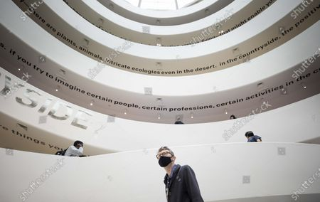 A man in a mask  walks through the main atrium of the Guggenheim Museum and past the exhibit 'Countryside: The Future' by Rem Koolhaas, which runs until 14 February 2021, on the first day that the museum is reopening to the public in New York, New York, USA, 30 September 2020. The Guggenheim, along with other museums and cultural institutions in the city, has been closed since March 2020 as a result of the coronavirus pandemic and is now reopening at 25 percent capacity.