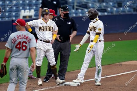 Stock Photo of San Diego Padres' Jurickson Profar, right, discusses a play with umpire Bill Miller, center, as San Diego Padres' Jake Cronenworth also stands on third after rundown during the eighth inning of Game 1 of a National League wild-card baseball series, in San Diego. Profar was called out on the play