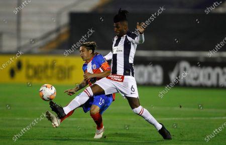 Jesus Meza of Venezuela's Estudiantes de Merida FC, left, and Carlos Ascues of Peru's Alianza Lima battle for the ball during a Copa Libertadores soccer match at the Alejandro Villanueva Stadium in Lima, Peru
