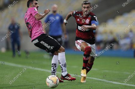 Cristian Pellerano of Ecuador's Independiente del Valle, left, fights for the ball with Giorgian Arrascaeta of Brazil's Flamengo during a Copa Libertadores soccer match at the Maracana stadium in Rio de Janeiro, Brazil