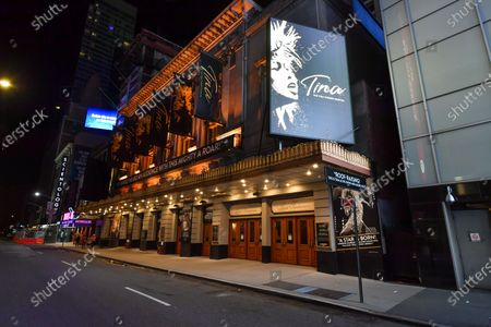 Stock Photo of Lunt-Fontanne Theatre at 205 W 46th St New York, NY remains lit up, but closed. Posters for 'Tina,' the Tina Turner Musical still adorn the theater.