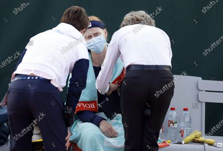 Alison Van Uytvanck of Belgium gets medical assistance as she plays Irina Bara of Romania during their women's second round match during the French Open tennis tournament at Roland Garros in Paris, France, 01 October 2020.