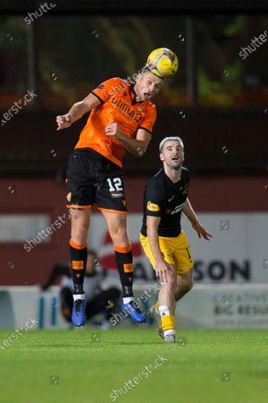 Ryan Edwards of Dundee United heads clear from Scott Robinson of Livingston; Tannadice Park, Dundee, Scotland; Scottish Premiership Football, Dundee United versus Livingston.