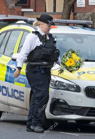 Stock Picture of A police officer with flowers. Metropolitan Police Commissioner Cressida Dick was at Croydon Custody Centre this morning for a visit. The murder investigation continues at pace after the death of police sergeant Matt Ratana almost a week ago at the Croydon Custody Centre in South London.