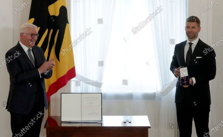 German President Frank-Walter Steinmeier, left, and the honored Thomas Hitzlsperger, right, pose for the media during a 'Order of Merit of the Federal Republic of Germany' handover ceremony at the Bellevue palace in in Berlin, Germany