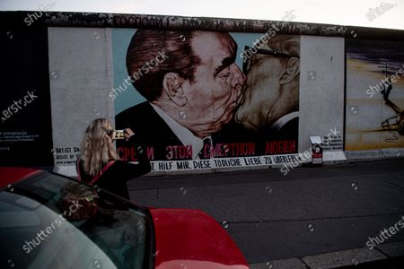 A visitor takes a picture of the graffiti painting 'Lord Help Me To Survive This Deadly Love' by Russian artist Dmitri Vrubel, which depicts the communist leaders Leonid Brezhnev and Erich Honecker kissing, at the East Side Gallery in Berlin, Germany, 30 September 2020. The German Day of Unity, marked annually on 03 October, celebrates the anniversary of the reunification of East and West Germany in 1990. The official construction of the Berlin Wall began on 13 August 1961. The roughly 43-kilometer barrier included watchtowers, checkpoints, barbed wire, and mines, creating a border strip separating the Western Allies' enclave of West Berlin from the rest of the city. The wall fell on 09 November 1989.