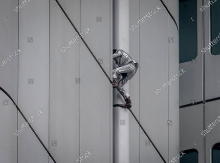 """Stock Image of French urban climber Alain Robert, well known as """"Spiderman"""", climbs up the Deutsche Bahn high-rise in central Frankfurt, Germany, . Robert was wearing a silver suit and cowboy boots"""