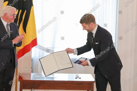 Stock Photo of German President Frank-Walter Steinmeier (L) hands over the Order of Merit of the Federal Republic of Germany to Thomas Hitzlsperger (R), the former professional soccer player, during a ceremony at the Schloss Bellevue in Berlin, Germany, 01 October 2020. The Order of Merit is the only German federal decoration.