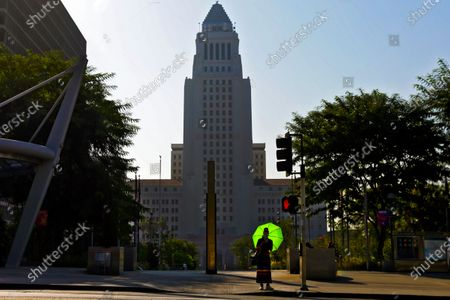 A lady's green umbrella shines under blazing sun on a very hot day in down town on Friday, Sept. 4, 2020 in Los Angeles, CA. (Irfan Khan / Los Angeles Times)