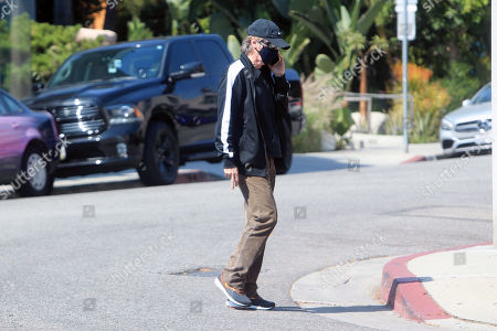 Dana Carvey is seen talking on his phone whilst crossing the street.