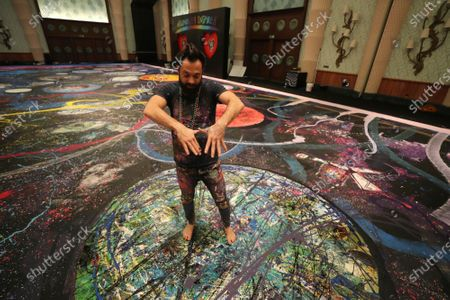 "British artist Sacha Jafri describes his painting titled ""The Journey of Humanity"" in Dubai, United Arab Emirates, . The painting with size of two football fields is part of his project ""Humanity Inspired"" and he hopes to raise 30 million USD to support health and education initiatives for children living in poverty worldwide"