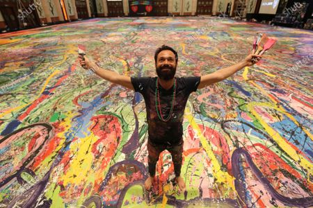 "British artist Sacha Jafri poses on his painting titled ""The Journey of Humanity"" in Dubai, United Arab Emirates, . The painting with size of two football fields is part of his project ""Humanity Inspired"" and he hopes to raise 30 million USD to support health and education initiatives for children living in poverty worldwide"