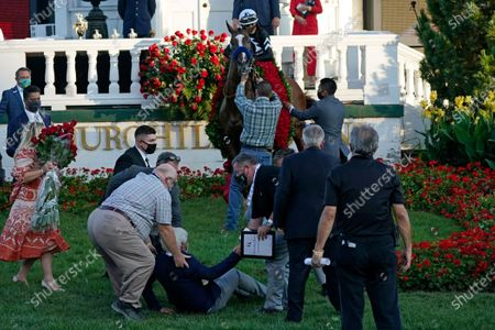 Stock Image of Trainer Bob Baffert is helped to get up after being knocked to the ground by his winning horse Authentic ridden by Jockey John Velazquez in the winners' circle after winning the 146th running of the Kentucky Derby at Churchill Downs in Louisville, Ky. Baffert is undefeated taking the Kentucky Derby winner to the Preakness, but for the first time in 20 years he'll do so without assistant trainer Jimmy Barnes, who broke his right wrist in a paddock accident at Churchill Downs