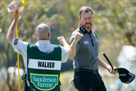 Jimmy Walker, right, fist bumps with his caddie following the first round of the Sanderson Farms Championship golf tournament in Jackson, Miss
