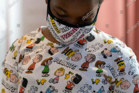 """Kerrin McCarthy, 14, paints a panel of a """"Peanuts"""" mural that will be placed in the outpatient pediatric floor of One Brooklyn Health at Brookdale Hospital, in the Brooklyn borough of New York. The beloved comic marks its 70th anniversary this week with new lesson plans, a new TV show and a philanthropic push that includes donating """"Peanuts"""" murals for kids to paint in 70 children's hospitals around the globe, from Brooklyn to Brazil"""