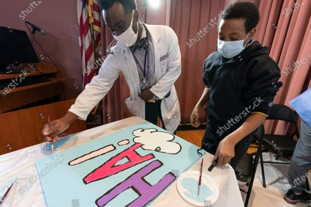 "Stock Photo of Pediatric resident Dr. Salome Wiredu, left and Jesse McCarty, 14, paint a panel of a ""Peanuts"" mural that will be placed in the outpatient pediatric floor of One Brooklyn Health at Brookdale Hospital, in the Brooklyn borough of New York. The beloved comic marks its 70th anniversary this week with new lesson plans, a new TV show and a philanthropic push that includes donating ""Peanuts"" murals for kids to paint in 70 children's hospitals around the globe, from Brooklyn to Brazil"