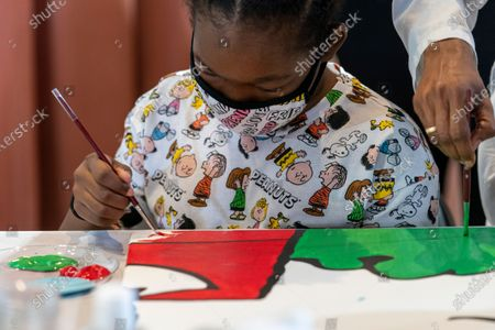 "Kerrin McCarthy, 14, paints a panel of a ""Peanuts"" mural that will be placed in the outpatient pediatric floor of One Brooklyn Health at Brookdale Hospital, in the Brooklyn borough of New York. The beloved comic marks its 70th anniversary this week with new lesson plans, a new TV show and a philanthropic push that includes donating ""Peanuts"" murals for kids to paint in 70 children's hospitals around the globe, from Brooklyn to Brazil"