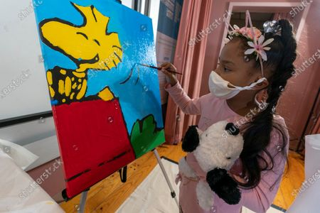 "Kaley Williams, 8, paints a panel of a ""Peanuts"" mural that will be placed in the outpatient pediatric floor of One Brooklyn Health at Brookdale Hospital, in the Brooklyn borough of New York. The virus pandemic won't stop Charlie Brown, Snoopy or the ""Peanuts"" gang from marking an important birthday and they're hoping to raise the spirits of sick kids while they celebrate. The beloved comic marks its 70th anniversary this week with new lesson plans, a new TV show and a philanthropic push that includes donating ""Peanuts"" murals for kids to paint in 70 children's hospitals around the globe, from Brooklyn to Brazil"
