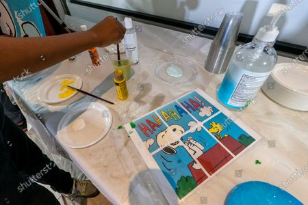 """Stock Photo of Jesse McCarty, 14, cleans his brush next to diagram of a """"Peanuts"""" mural he is helping to paint that will be placed in the outpatient pediatric floor of One Brooklyn Health at Brookdale Hospital, in the Brooklyn borough of New York. The virus pandemic won't stop Charlie Brown, Snoopy or the """"Peanuts"""" gang from marking an important birthday and they're hoping to raise the spirits of sick kids while they celebrate. The beloved comic marks its 70th anniversary this week with new lesson plans, a new TV show and a philanthropic push that includes donating """"Peanuts"""" murals for kids to paint in 70 children's hospitals around the globe, from Brooklyn to Brazil"""