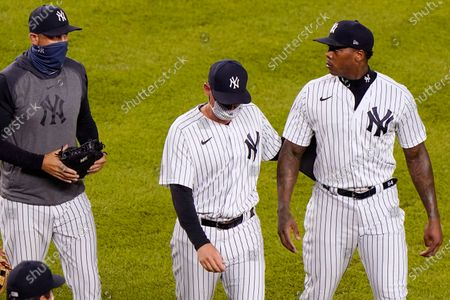 """New York Yankees manager Aaron Boone, left, keeps watch on New York Yankees relief pitcher Aroldis Chapman as a teammate escorts Chapman off the field after benches cleared following a pitch Chapman threw close to Tampa Bay Rays pinch hitter Michael Brosseau's head during the ninth inning of a baseball game at Yankee Stadium in New York. The Rays wear blue T-shirts with four horses lined up behind a fence, a reference to Tampa Bay manager Kevin Cash declaring """"I've got a whole damn stable full of guys that throw 98 miles an hour"""" in response to Aroldis Chapman throwing near the Mike Brosseau's head on Sept. 1"""