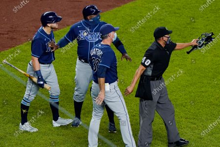 """Tampa Bay Rays pinch-hitter Michael Brosseau, left, is restrained by a coach as second base umpire Chad Fairchild (4) warns New York Yankees relief pitcher Aroldis Chapman to stay away from Brosseau as the two players exchanged words following the Rays' 5-3 loss to the Yankees in a baseball game at Yankee Stadium in New York. The altercation started after Chapman threw a high pitch at Brosseau. The Rays wear blue T-shirts with four horses lined up behind a fence, a reference to Tampa Bay manager Kevin Cash declaring """"I've got a whole damn stable full of guys that throw 98 miles an hour"""" in response to Aroldis Chapman throwing near the Mike Brosseau's head on Sept. 1"""