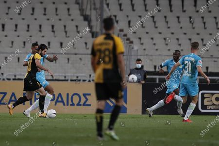 AEK's Karim Ansarifard, left, scores his side's second goal during the Europa League playoff soccer match between AEK Athens and VfL Wolfsburg at the Olympic stadium in Athens, . AEK Athens won 2-1