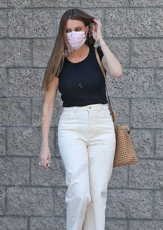 Sofia Vergara steps out wearing her pink mask and carring a tan bag
