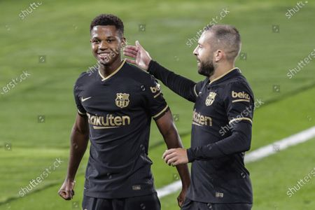 Barcelona's Ansu Fati, left, is congratulated by teammate Jordi Alba after scoring the opening goal during the Spanish La Liga soccer match between RC Celta and FC Barcelona in Vigo, Spain