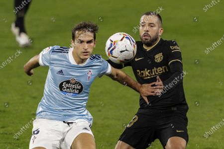 Celta Vigo's Denis Suarez, left, duels for the ball with Barcelona's Jordi Alba during the Spanish La Liga soccer match between RC Celta and FC Barcelona in Vigo, Spain