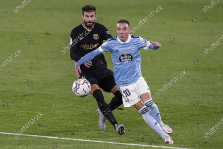 Celta Vigo's Iago Aspas, right, duels for the ball with Barcelona's Gerard Pique during the Spanish La Liga soccer match between RC Celta and FC Barcelona in Vigo, Spain