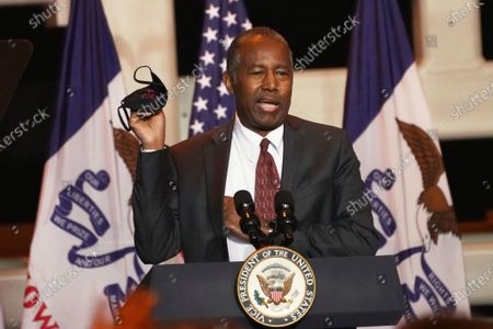 Secretary of Housing and Urban Development Ben Carson holds up a face mask during a Make America Great Again event in Carter Lake, Iowa