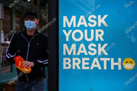 A man wearing a face mask as a preventive measure walks past 'Mask Your Mask Breath', a Wrigley's Extra Peppermint Gum advert.