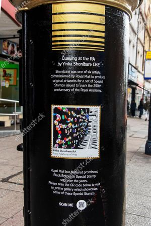Stock Photo of A Royal Mail postbox from the time of King George VI reign in Brixton, South London has been painted as part of Black History Month in October. It is one of four to have been painted others are in Glasgow, Belfast, & Cardiff. It features 'Queuing at the RA' by British-Nigerian artist Yinka Shonibare, one of six artists who were commissioned by the Royal Mail to produce original artworks for a set of special stamps issued to mark the 250th anniversary of the Royal Academy (RA).