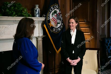Stock Photo of Judge Amy Coney Barrett, President Donald Trump's nominee for the US Supreme Court, looks on during a meeting with Senator Deb Fischer (L) (R - NE) at the US Capitol in Washington, DC, USA, 01 October 2020.