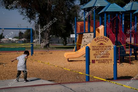 """Fernando Olvera, 5, pulls a string of yellow caution tape at a playground closed due to the coronavirus pandemic, in South Central Los Angeles. California's plan to safely reopen its economy will begin to require counties to bring down coronavirus infection rates in disadvantaged communities that have been harder hit by the pandemic. The complex new rules set in place an """"equity metric"""" that will force larger counties to control the spread of the virus in areas where Black, Latino and Pacific Islander groups have suffered a disproportionate share of the cases due to a variety of socioeconomic factors"""