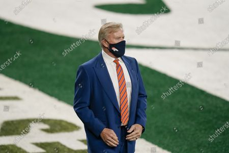 John Elway, president of football operations for the Denver Broncos, watches his team warm up before an NFL football game against the New York Jets, in East Rutherford, N.J