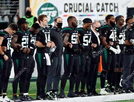 New York Jets head coach Adam Gase stands with his player during the national anthem before an NFL football game against the Denver Broncos, in East Rutherford, N.J