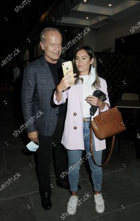 Kelsey Grammer takes photos with fans outside Scott's restaurant.