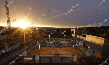 The sun sets over Paris as play continues on Court 7 (foreground) between Tsvetana Pironkova of Bulgaria and Barbora Krejcikova of the Czech Republic in the women's third round at the French Open tennis tournament at Roland Garros in Paris, France, 02 October 2020