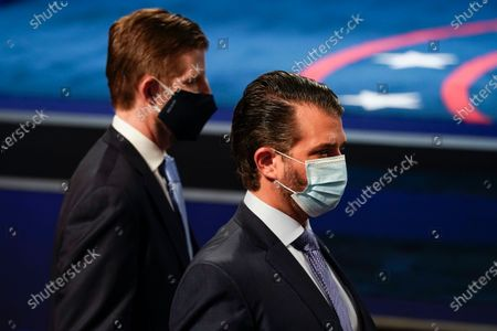 Eric Trump, left, and Donald Trump Jr., right, sons of President Donald Trump, wearing face masks at they arrive to take their seats for the first presidential debate, at Case Western University and Cleveland Clinic, in Cleveland, Ohio